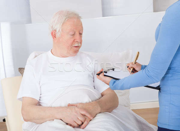 Caretaker With Clipboard Attending Senior Patient Stock photo © AndreyPopov