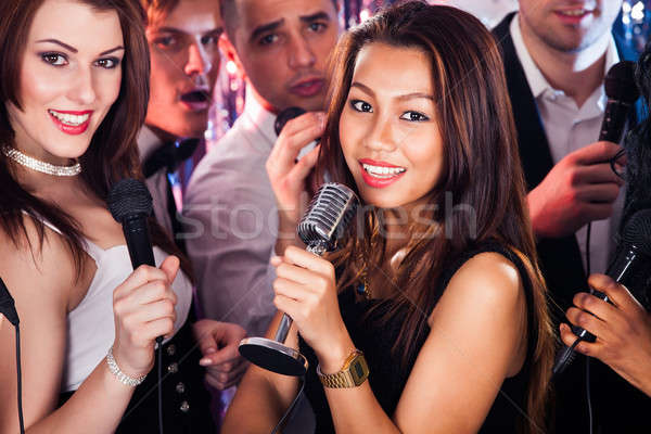 Friends Singing Into Microphones At Karaoke Party Stock photo © AndreyPopov
