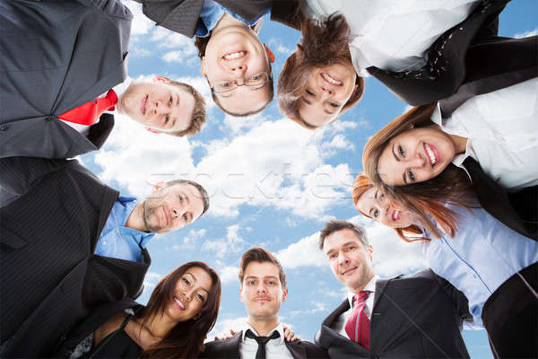 Multiethnic Businesspeople Forming Huddle Against Sky Stock photo © AndreyPopov