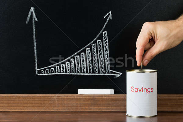 Stock photo: Close-up Of A Person Inserting Coin In Saving Can