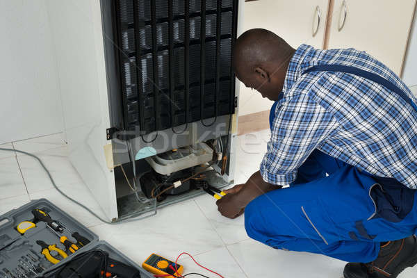 Technician Fixing Refrigerator With Worktool Stock photo © AndreyPopov
