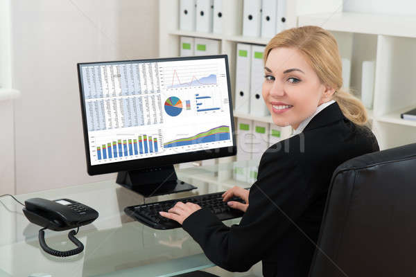 Businesswoman Smiling While Working On Computer Stock photo © AndreyPopov