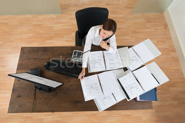 Stock photo: Businesswoman Attending Call While Calculating Finance