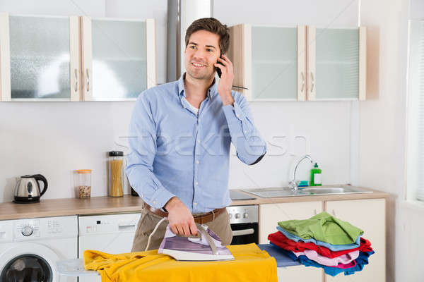 Man Talking On Mobile Phone While Ironing Clothes Stock photo © AndreyPopov