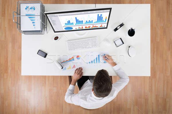 Businessman Analyzing Statistical Graphs Stock photo © AndreyPopov