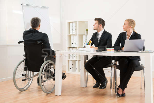 Handicapped Businessman Explaining To His Colleagues Stock photo © AndreyPopov