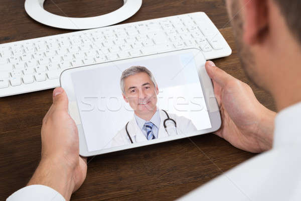 Businessperson Videochatting With Senior Doctor Stock photo © AndreyPopov
