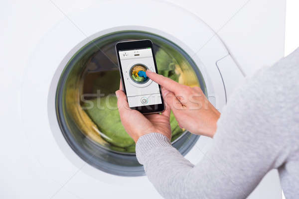 Woman Using Mobile Phone To Operate Washing Machine Stock photo © AndreyPopov