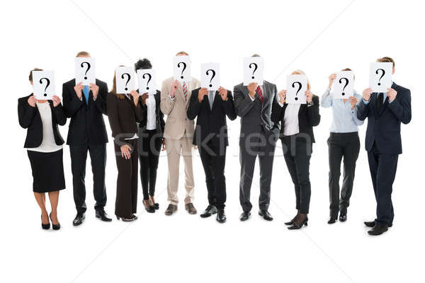 Business Team Hiding Faces With Question Mark Signs Stock photo © AndreyPopov