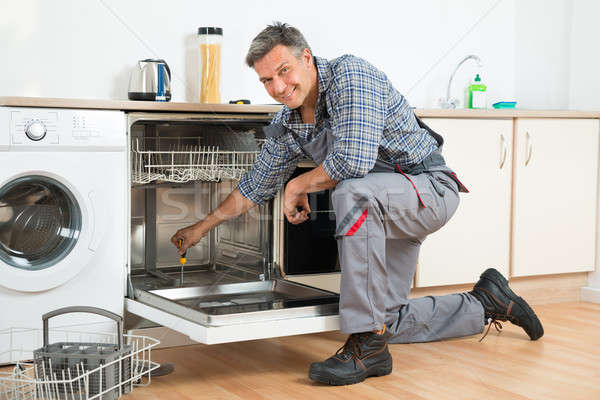 repairman repairing dishwasher with screwdriver in kitchen stock photo andriy popov. Black Bedroom Furniture Sets. Home Design Ideas