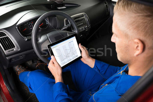 Mechanic Sitting In Car Looking At Digital Tablet Stock photo © AndreyPopov