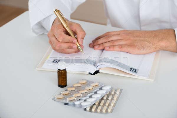 Médecin écrit ordonnance table clinique Photo stock © AndreyPopov