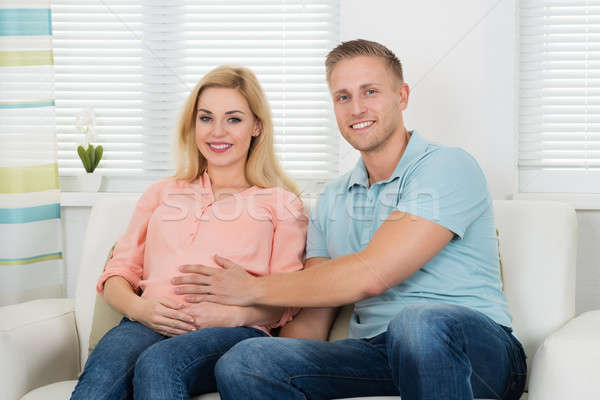 Happy Expectant Couple Sitting On Sofa At Home Stock photo © AndreyPopov