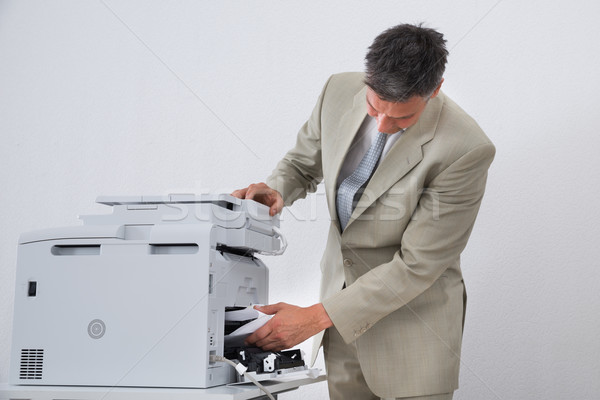 Businessman Removing Paper Stuck In Printer Stock photo © AndreyPopov