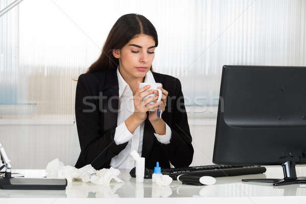 Sick Businesswoman Holding Cap Of Tee At Desk In Office Stock photo © AndreyPopov