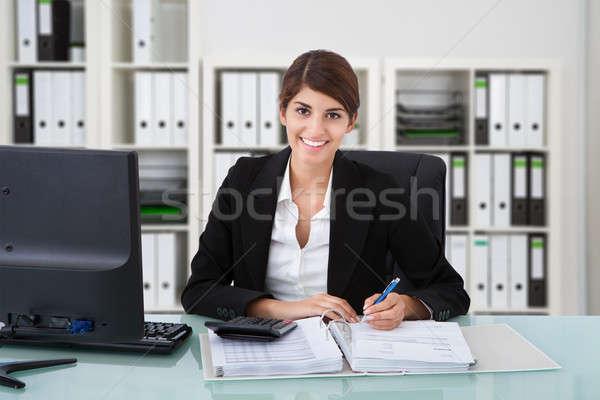 Female Accountant Writing On Documents Stock photo © AndreyPopov
