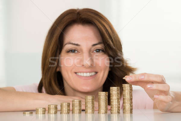 Happy Woman Stacking Coins At Desk Stock photo © AndreyPopov