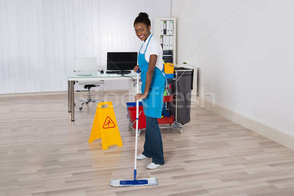 Female Janitor Mopping Floor In Office Stock photo © AndreyPopov