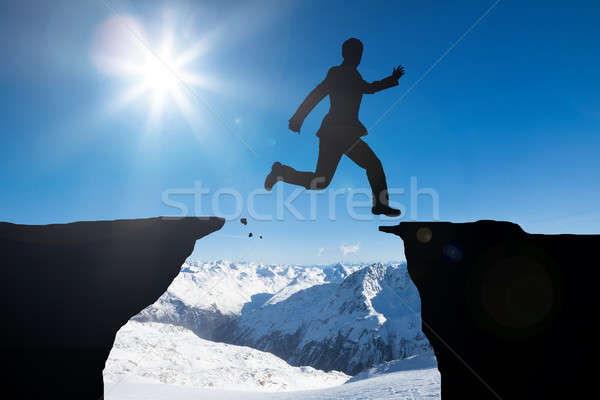 Man Jumping Over Mountains Stock photo © AndreyPopov