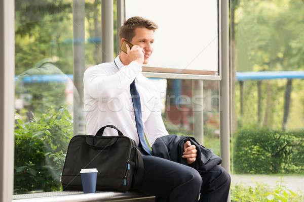 Biznesmen mówić telefonu komórkowego przystanek autobusowy młodych czeka Zdjęcia stock © AndreyPopov