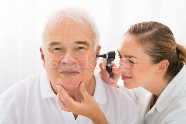Doctor Looking At Patient's Ear Through Otoscope Stock photo © AndreyPopov