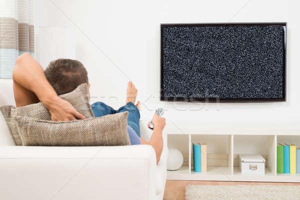 Homem controle remoto relaxante sofá televisão Foto stock © AndreyPopov