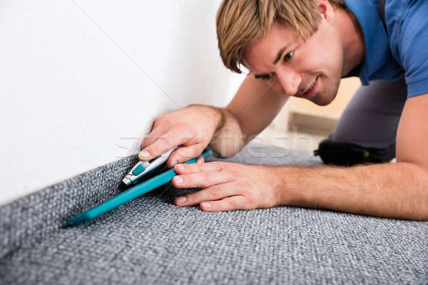 Craftsman Cutting Carpet With Cutter Stock photo © AndreyPopov
