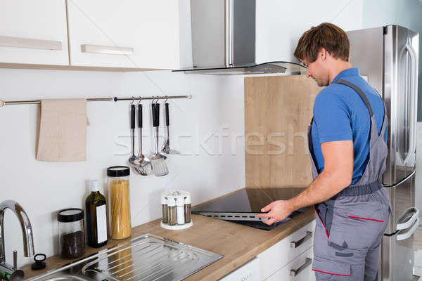 Man In Overall Installing Induction Stove Stock photo © AndreyPopov