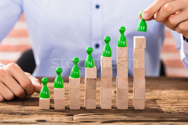 Businessman Arranging The Figures On Block Stack Stock photo © AndreyPopov