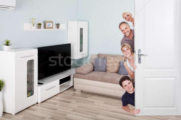 Portrait Of Happy Family Peeking From Door Stock photo © AndreyPopov