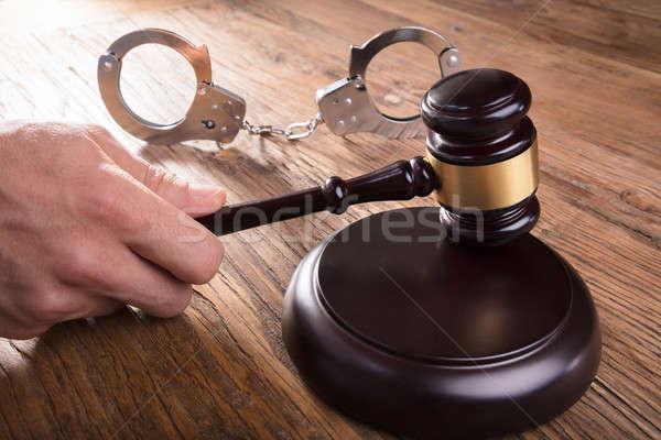 Rechter hand hamer handboeien houten bureau Stockfoto © AndreyPopov