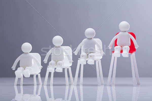 Close-up Of Human Figures Sitting On Increasing Chairs Stock photo © AndreyPopov