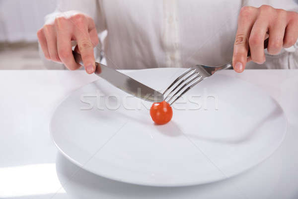 Person Cutting Cherry Tomato On Plate Stock photo © AndreyPopov