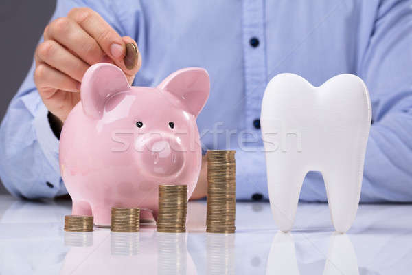 White Tooth Beside Man Inserting Coin In Piggy Bank Stock photo © AndreyPopov