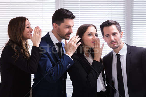 Businesspeople Gossiping Into Young Man's Ear Stock photo © AndreyPopov