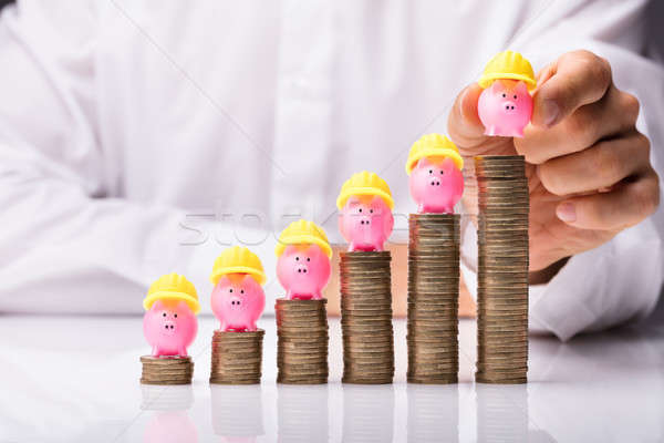 Hand Placing Piggybank With Yellow Hardhat On Stacked Coins Stock photo © AndreyPopov