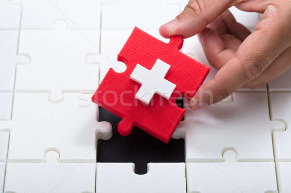 Man's hand solving jigsaw puzzle with red piece Stock photo © AndreyPopov