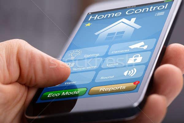 Mobiltelefon otthon irányítás alkalmazás személyek kéz Stock fotó © AndreyPopov
