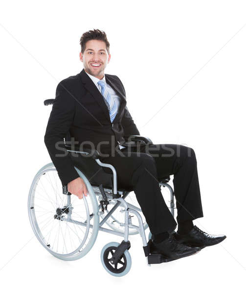 Smiling Young Businessman Sitting On Wheelchair Stock photo © AndreyPopov