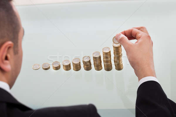 Businessman Stacking Coins In Increasing Order Stock photo © AndreyPopov