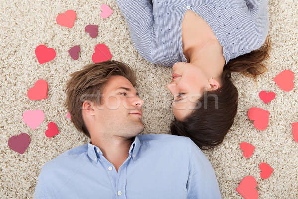 Couple Surrounded With Hearts Lying On Rug Stock photo © AndreyPopov