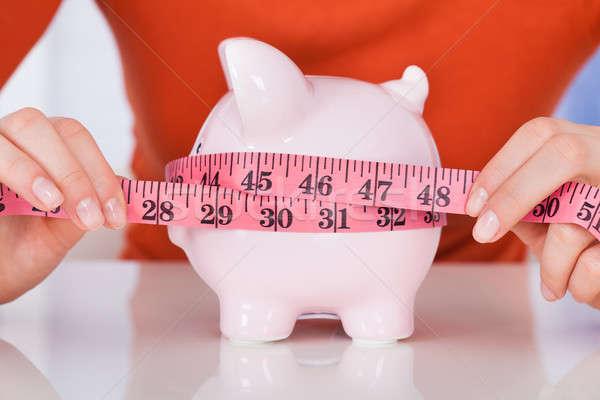 Woman Measuring Piggybank With Measure Tape Stock photo © AndreyPopov