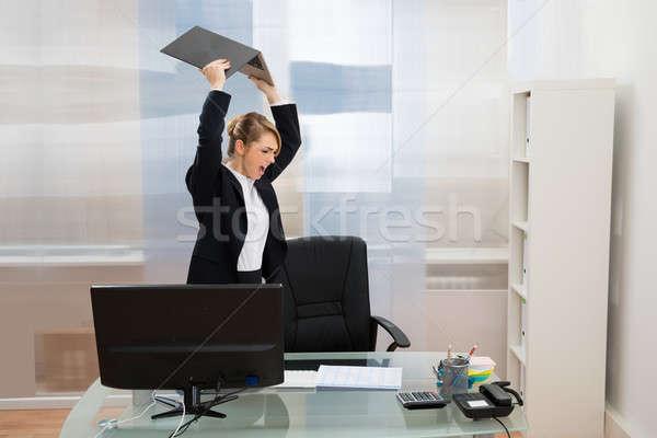 Enojado mujer de negocios portátil pie escritorio Foto stock © AndreyPopov