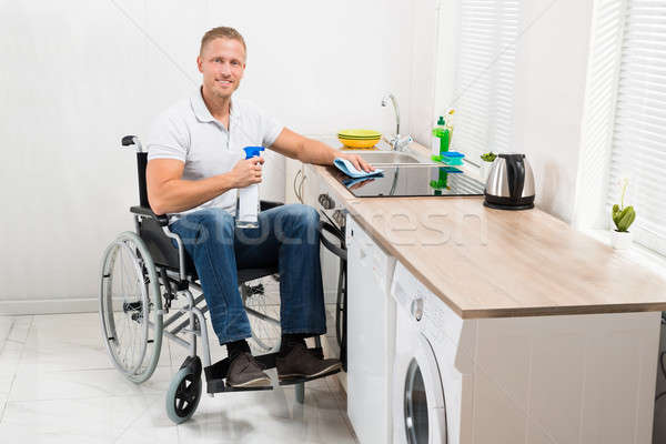 Man On Wheelchair Cleaning Induction Stove Stock photo © AndreyPopov