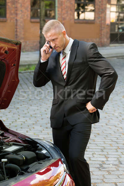 Stressed Young Man With His Breakdown Car Calling On Cellphone Stock photo © AndreyPopov