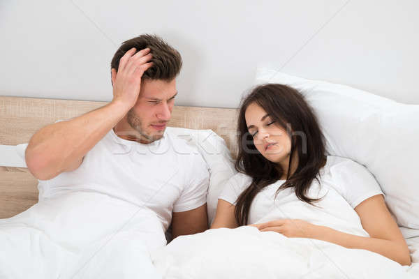 Man Looking At Woman Snoring In Bed Stock photo © AndreyPopov