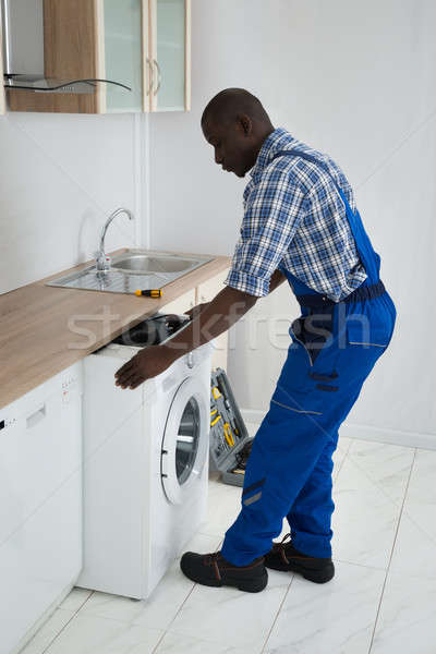 Technician Pulling Washing Machine In Kitchen Stock photo © AndreyPopov