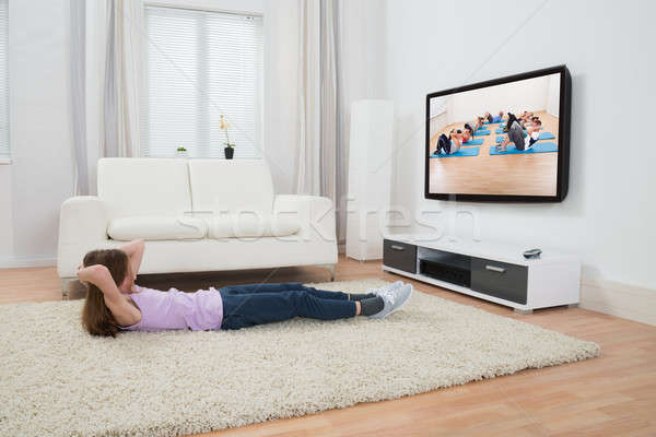Girl Exercising In Front Of Television Stock photo © AndreyPopov
