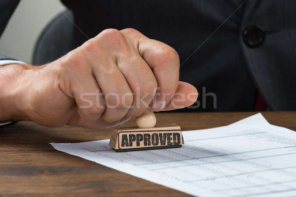 Businessman Stamping Document Marked With Approved Stock photo © AndreyPopov