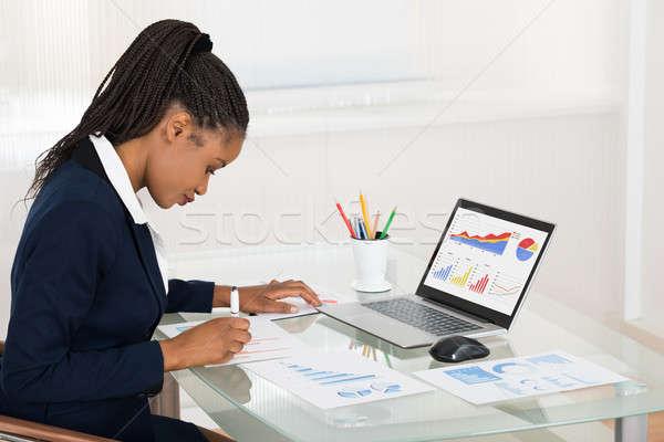 üzletasszony laptop grafikon irodai asztal fiatal afrikai Stock fotó © AndreyPopov
